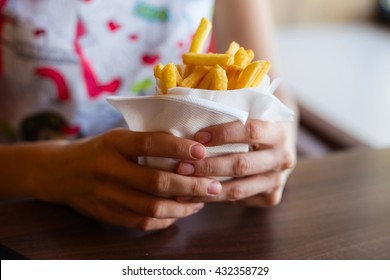 girl holding fries. Fast food at the cafe table