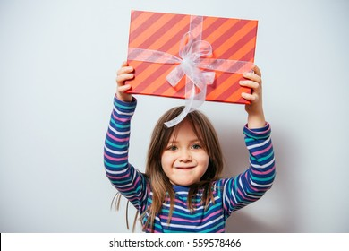 girl holding a gift. a child with a gift