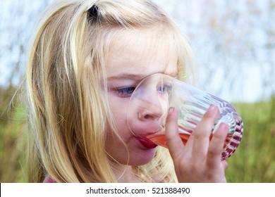 Girl holding glass drinking lemonade. Happy child at summer