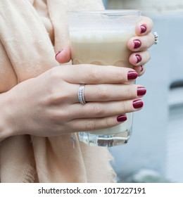 The girl is holding a glass of latte