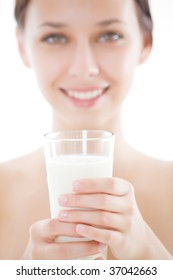 Girl holding a glass of milk in front of her. Focus is on the glass