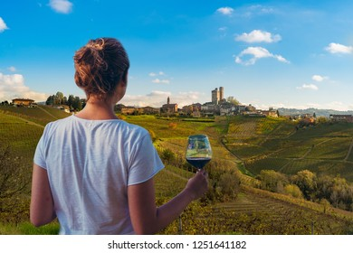 girl holding a glass of red wine looking amazing green vineyards in the italian region of Piedmont, Alba, Serralunga d'alba, Langhe and Monferrato region, Italy
