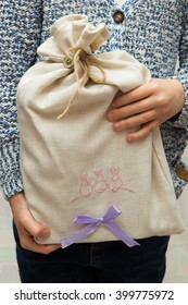 The girl holding gray bag with a gift.