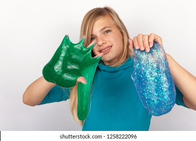 Girl holding a green and a blue glitter slime