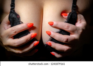 girl holding hand with red nails her Breasts in bra black on black background