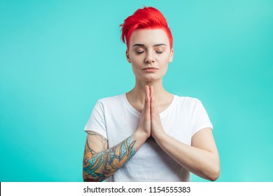 girl holding hands together and doing yoga. namaste position. free time. woman practising yoga. meditation with closed eyes. hipster is trying to calm down. copy space. isolated blue background