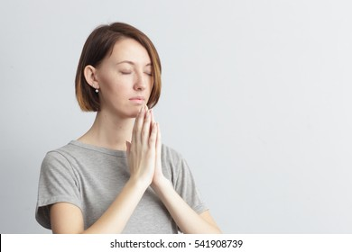 Girl holding hands together, elbows to the sides. Eyes closed. Meditate or make a wish, trying to calm down.
