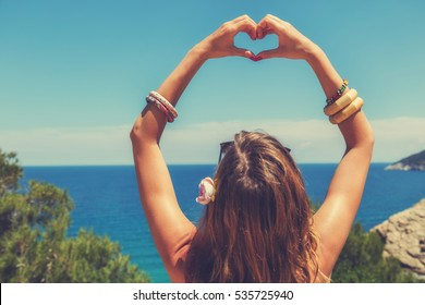 Girl holding a heart shape for the summer time.