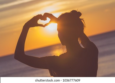 Girl holding a heart - shape symbol with her hands / fingers.