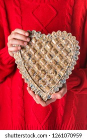 Girl holding a heart shaped homemade  birdseed cake. Help people to animals. Selective focus.