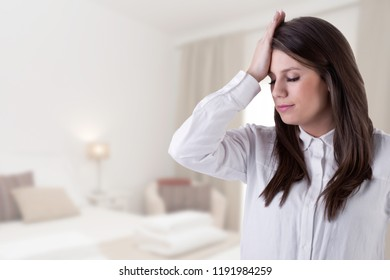 Girl holding her hand to her forehead in a sign of trouble in a house