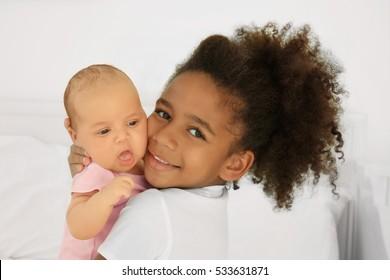 Girl holding her little sister, closeup