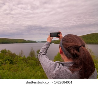 A girl holding her phone up to take a picture of the Allegheny Reservoir in Warren County, Pennsylvania, USA on an overcast spring day