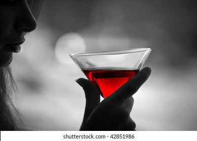 The girl is holding in his hand a glass of alcoholic beverage, red wine in glass ( black white photo)
