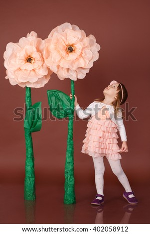 Girl holding huge flower looking him pretty stock photo edit now girl holding a huge flower and looking at himetty little girl standing on a mightylinksfo