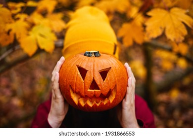 Girl holding jack-o-lantern in front of face. Carved halloween spooky pumpkin. Gold autumn colors.