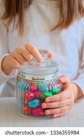 Girl holding jar of coloured foil wrapped  chocolate eggs  candy
