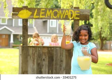 Girl holding lemonade in front of lemonade stand