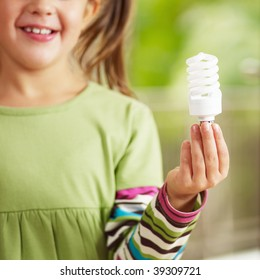 Girl holding light bulb and smiling. Selective focus