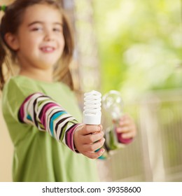 Girl holding light bulb and smiling. Selective focus, copy space