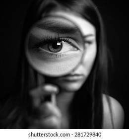 A girl holding a magnifying glass on a dark background, scary big eyes