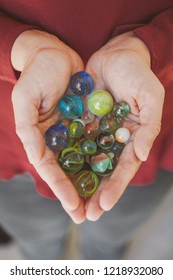 Girl holding marbles. Closeup view of colorful glass marbles as background.
