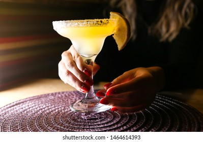 Girl holding margarita cocktail on the table in the restaurant. Alcoholic drinks. Beautiful hands.