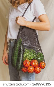 Girl holding mesh shopping bag with vegetables. Sustainable, zero waste and plastic free lifestyle.