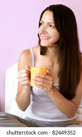 Girl holding a mug in bed