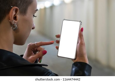 Girl holding on smartphone with empty blank screen monitor on the background bokeh light in street atmosphere, freelancer hipster using in female hands smart phone with blank template, blur