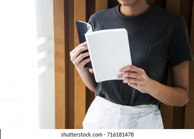 a girl holding the open book and reading it