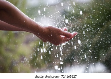 Girl holding out hands to rain.
