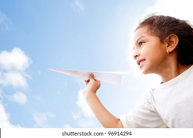 Girl holding a paper airplane and dreaming aboyt flying