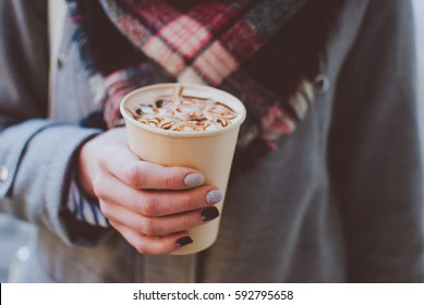 The girl holding the paper cup of coffee with milk and caramel in her tender hand. Sunny spring afternoon.