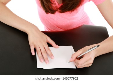 girl holding pen writing on white note cards