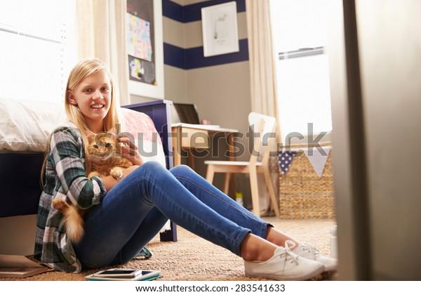 Girl holding pet cat in her bedroom