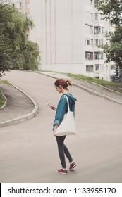Girl holding phone and blank eco or shopping bag
