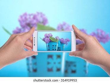Girl holding the phone and photographed flowers. Mobile technology. Mobile Photography