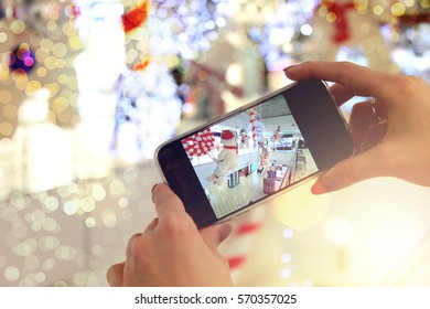Girl holding the phone and take pictures with bokeh closeup