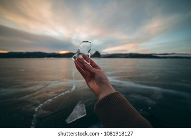 girl holding a piece of ice. early on the morning girl has found the ice on the lake. Lake Baikal in Siberia.