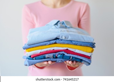 girl is holding a pile of washed and ironed clothes in her hands on a white background