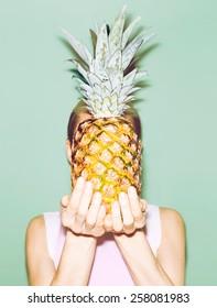 Girl holding Pineapple. Fashionable stylish summer