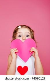 Mädchen, die rosafarbenes Papierherz in Händen halten