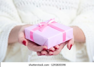 girl holding a present in hands, woman with gift box wrapped in decorative pink paper on white isolated background, concept winter holiday