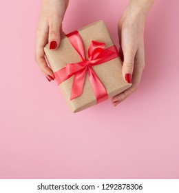 girl holding a present in hands, women with gift box in hands wrapped in decorative paper on a pastel colored pink background, top view, concept holiday and gifts