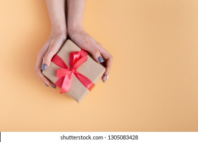 girl holding a present in hands, women with gift box in hands wrapped in decorative craft paper on a pastel colored background, top view, concept holiday