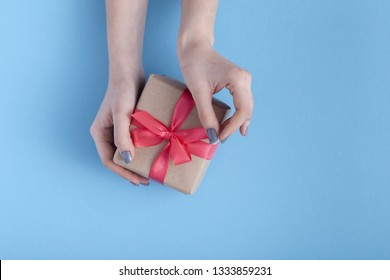 girl holding a present in hands, women with gift box with a tied red ribbon bow in hands on a pastel colored blue background, top view, concept holiday, love and care