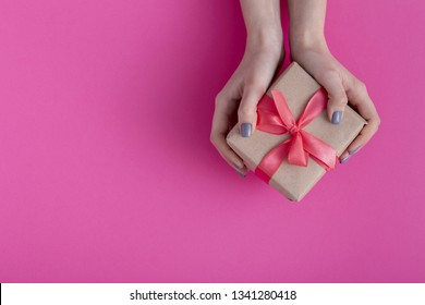 girl holding a present in hands, women with gift box in hands wrapped in decorative craft paper with a tied red ribbon bow on colored cardboard background, top view, concept holiday, love and care
