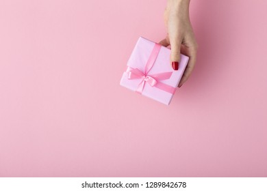girl holding a present in hands, women's hands open the box wrapped in decorative paper on a pastel colored pink background, top view, concept holiday and gifts