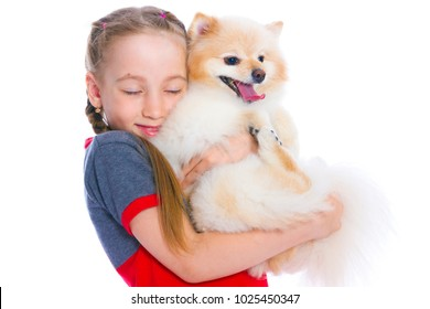 Girl holding a puppy on her hands on a white background